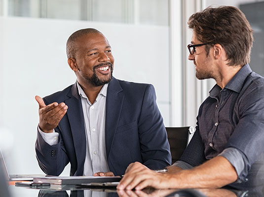 Businessman smiling and talking to his client in a conference room.